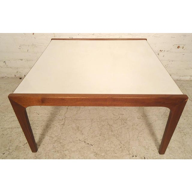 Vintage table with laminate top and sculpted legs. Accenting white top with walnut frame. (Please confirm item location -...