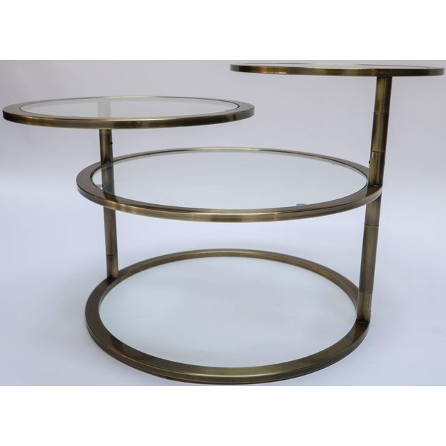 Three tiered brass coffee or side table with glass shelves. The top two shelves rotate 360 degrees. Measurements with...