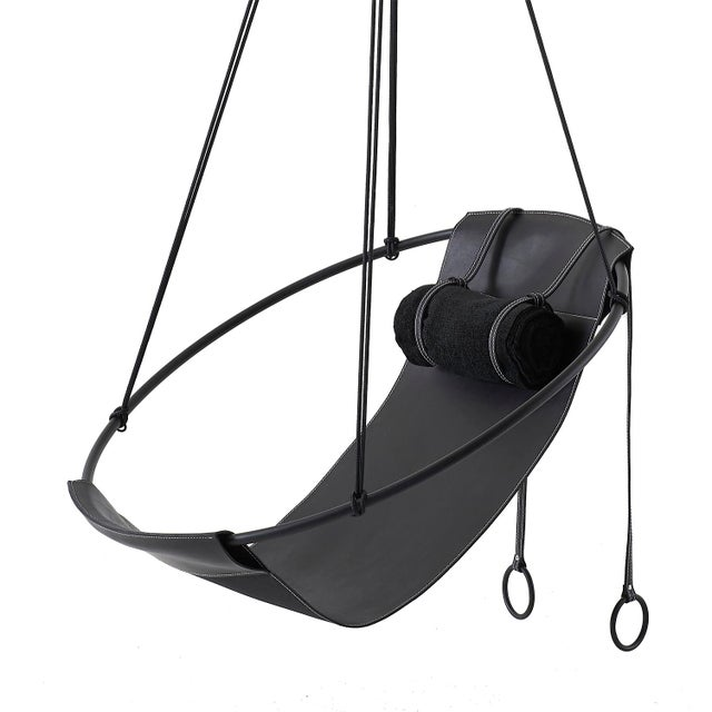Stripped away from all excess, this hanging chair has a circular frame with a single sheet of leather or fabric hanging...