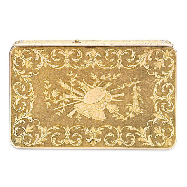 This special and important Swiss gold music box is chased and engraved with a set of musical instruments surrounded by...