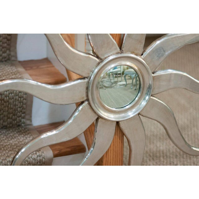A whimsical, sunburst mirror in silvered wood with wavy rays and a molded centre.