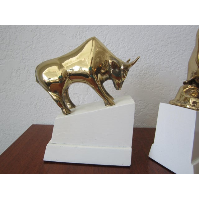 Polished brass bull and bear bookends mounted on high gloss white lacquered wood bases. Dynamic sharp contrast between the...
