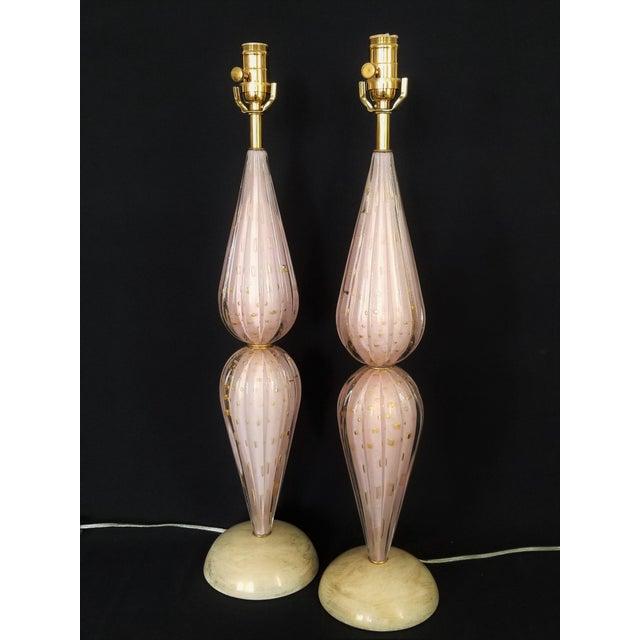 Offering a RARE pair of pink and gold Murano glass lamps by Alfredo Barbini, circa 1950s. These elegant lamps are in...