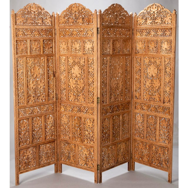 Circa 1870's Indian wood folding screen has four panels with elaborate open work carved panels with leaf motif. Excellent...