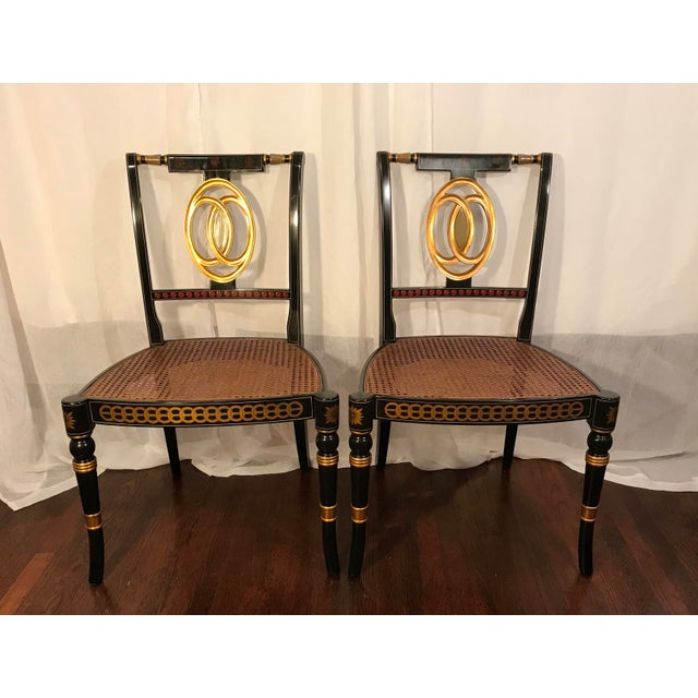 Exquisite Pair of Hand Painted Black Lacquered Regency Chairs With Cane Seats. These gorgeous chairs feature hand painted...