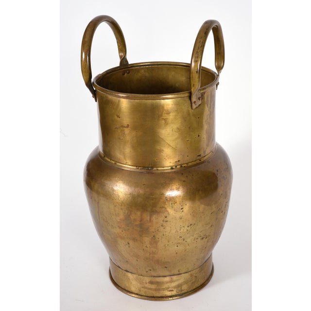 Mid-20th century indoor / outdoor brass umbrella stand or cane stand with two side handles. The umbrella stand is in good...