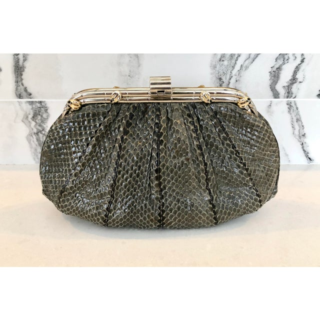 Judith Leiber grey python clutch with gold accented silver hardware. Whimsical frogs with onyx eyes accent the metal. Soft...