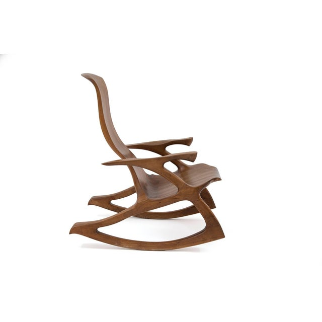 Solid walnut studio crafted rocking chair. This example has sculpted arms and frame with inset dove tailing and subtly...