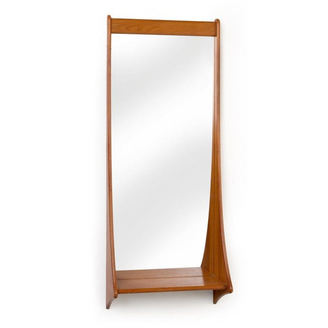 A tall entry way mirror in teak with integral shelf. By Pedersen and Hansen. Danish, circa 1950. Please call gallery for...