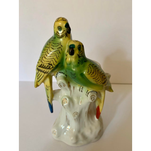 A vintage porcelain bud vase with great detail. It features green parakeet birds, white tree stumps, flowers and metallic...