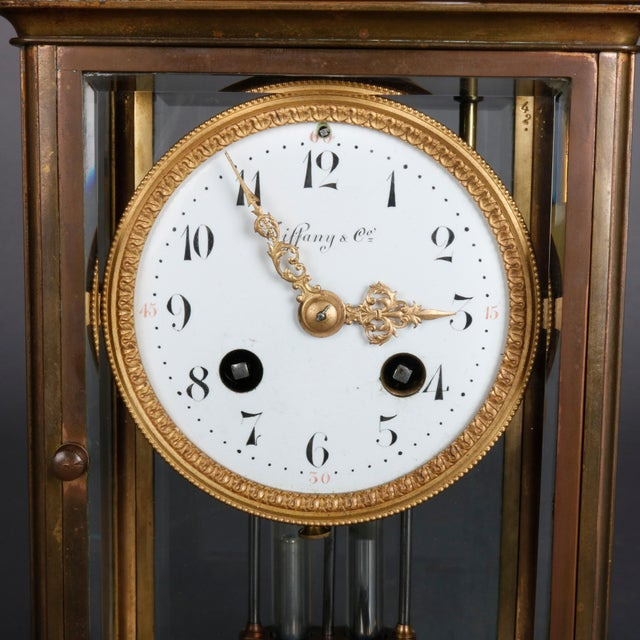 An antique regulator mantel clock by Tiffany & Co. offers brass frame with works house in beveled crystal case, face...