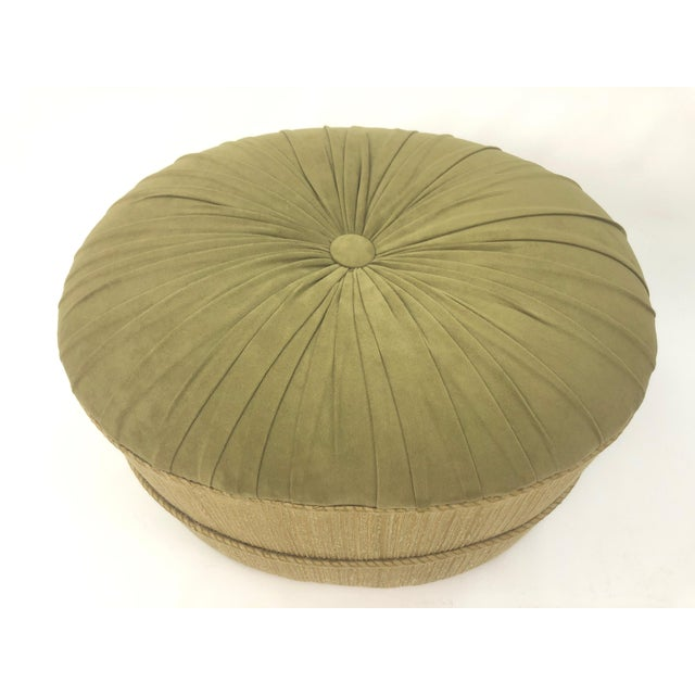 A stylish oval pouf or ottoman in a wonderful olive green ultrasuede having single button and pleating on top and a...