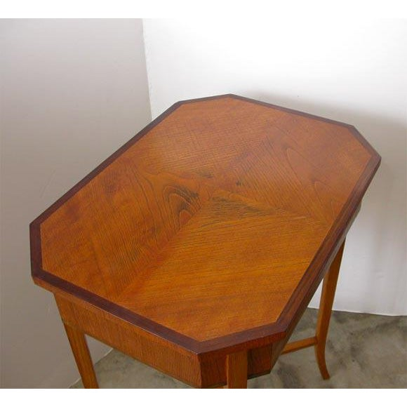 This sweet Swedish occasional table has a top with quartered veneer panels edged with walnut over a frieze having one...