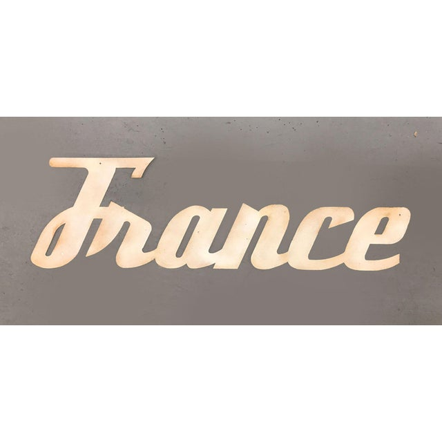 """1960s metal sign in cursive script reading """"France"""" pulled from an old Atlanta travel agency. Flat sheet metal was..."""