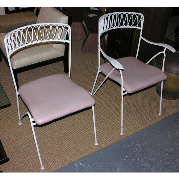 A set of fourteen wrought iron ribbon back dining chairs comprised of twelve sides and two armchairs. By Maurizio...