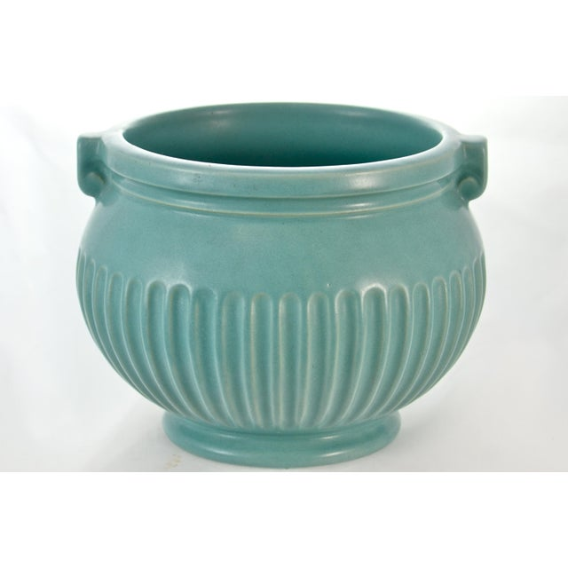Matte glaze turquoise blue catchall with a fluted body and petite Grecian style handles. No maker's mark. Light wear with...