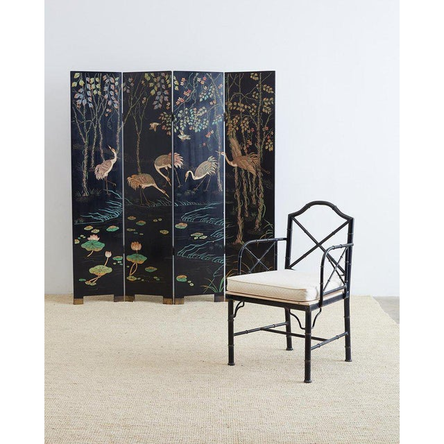 Gorgeous Chinese four-panel Coromandel screen featuring red-crowned cranes among trees and lotus blossoms. Dramatic color...