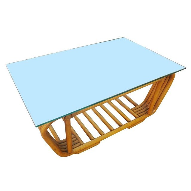 Made circa 1947, this five-pole rattan coffee table has an unusual bent rattan round base. The five rattan poles are...