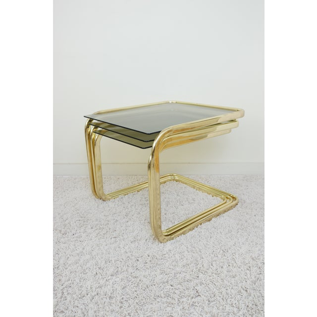 Here's a set of three vintage nesting tables, made of gold-chrome plated steel and glass. In good condition, with some...