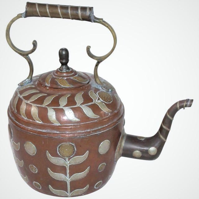 This highly decorated handmade copper kettle has appliqued sunflowers in silver and brass cutouts. The handle and stem is...