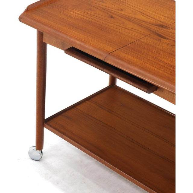 """Midcentury Danish modern expandable teak bar cart on wheels with one 12"""" extension board."""