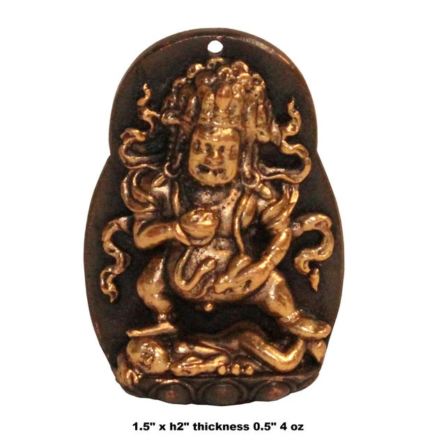 This is a metal pendant crafted with a Tibetan Zambala Jambhala motif. The background is in brown color and the Buddha is...