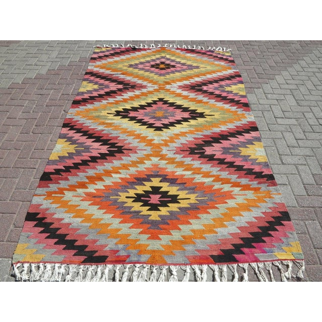 This Turkish Kilim rug hosts an intriguing pallet of vibrant rich and pastel colorways complementing a very turkish sense...
