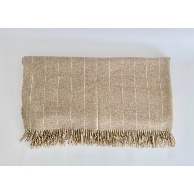New English Bronte Merino lambswool fringed throw in a neutral oatmeal with white stripes color way. Soft mid-weight throw...