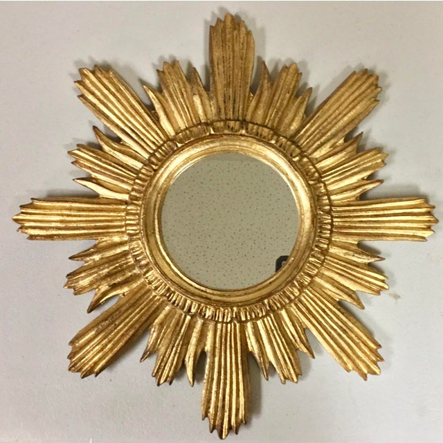 1960s Hollywood Regency sunburst mirror with the original label. The frame is giltwood.