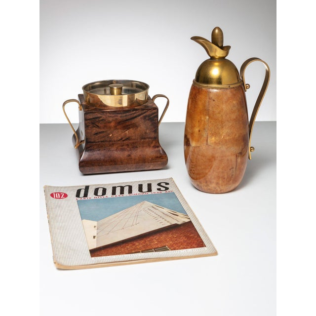 Rare set of ice bucket and pitcher by Aldo Tura. Brass details and shiny parchment finish.
