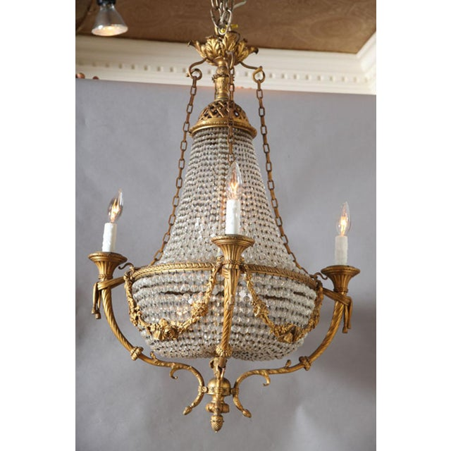 Exquisite Empire chandelier, having a frame of finely chased gilt bronze, basket shape, draped in beaded crystals; floral...