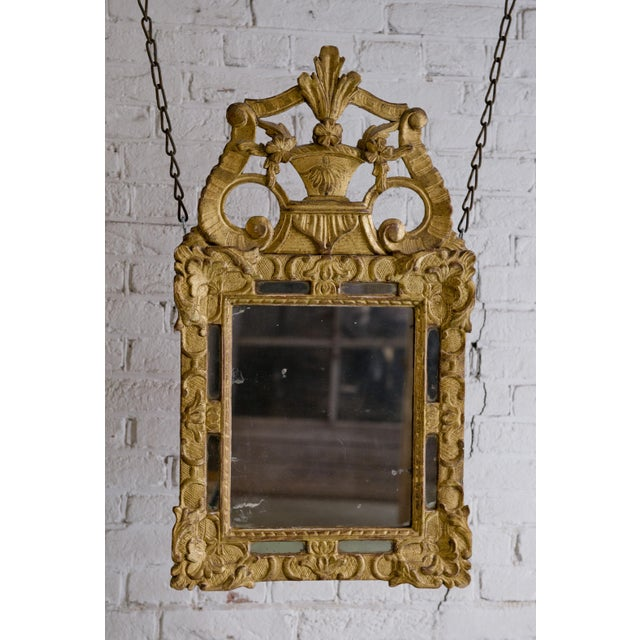 Carved gilt wood mirror, Louis XIV. Provenance France. This Louis XIV mirror is exuberant, symmetrical and nicely...