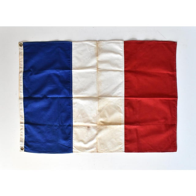 A vintage, mid-century French flag, tricolore with the red, white, and blue, hand-sewn in cotton, with metal grommets.