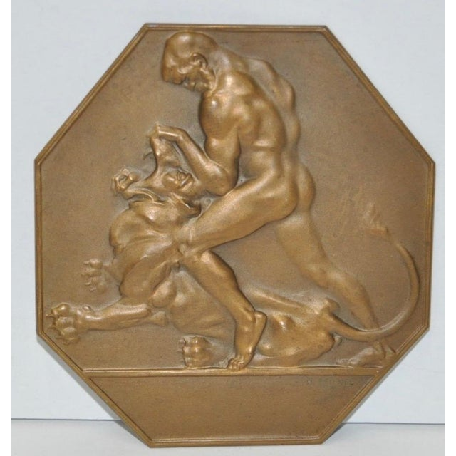 Circa 1920s, or earlier, fabulous bronze plaque shows a man wrestling a lion. This would be a unique, and wonderful gift...
