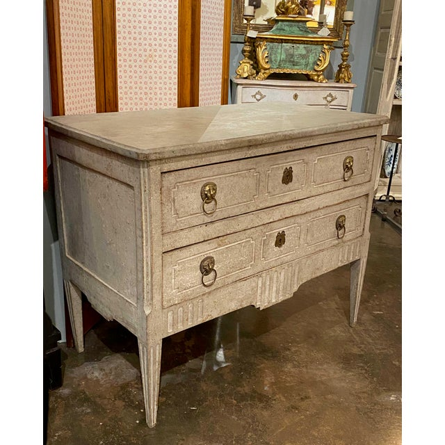 18th century Neoclassical carved and painted commode with original locks and brass lion head hardware. Circa 1775.