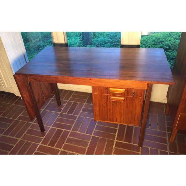 Hard to find in rosewood drop leaf desk made in Denmark. Top slides to level the drop leaf for more surface writing space....