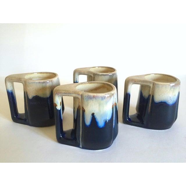 This set of four vintage Mid Century Organic Modern indigo blue drip glaze ceramic handled mugs are a very special and...