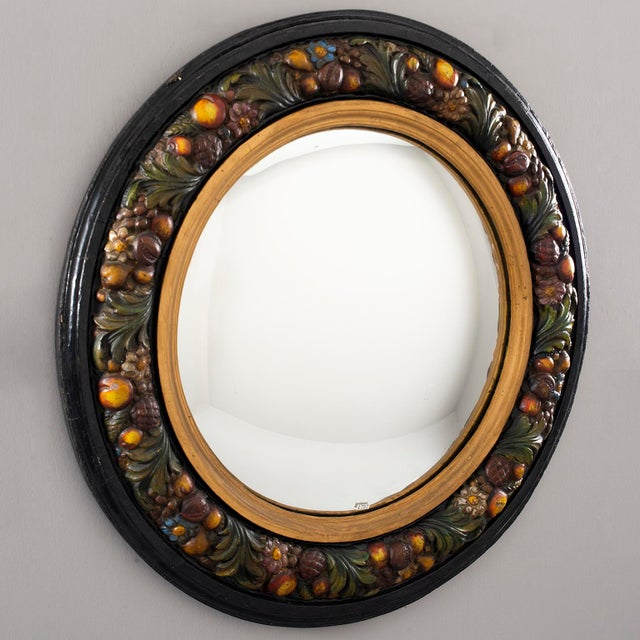 Circa 1930s large round French mirror has a traditional Barbola style frame of fruit and flowers on a black background...
