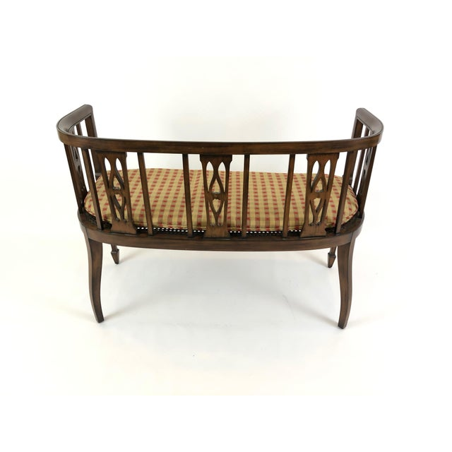 Refined fruitwood settee having lovely curved back with open fretwork, tapered legs and excellent condition caned seat....