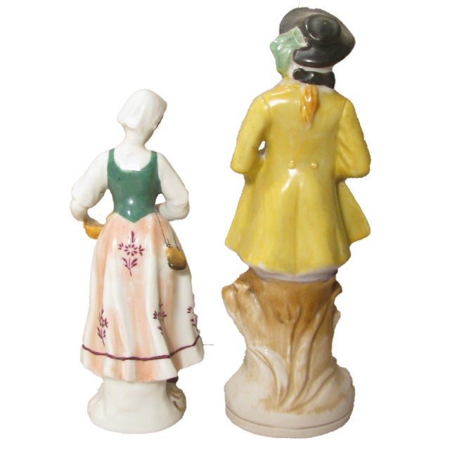 Charming pair of Staffordshire style figurines -- a fishmonger lass and a colonial lad who has come courting with a lovely...