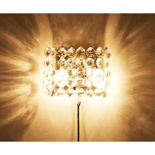 This vintage wall sconce was made by Bakalowits in Austria in the 1960s. It has a nickel-plated steel frame and crystal...