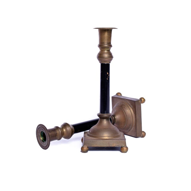 A chic pair of Antique brass and black candlesticks. They are classic and will bring an extra special glow to any room.