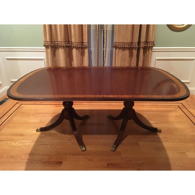 Traditional and beautiful, this Ethan Allen dining room table and chairs set, with custom protective table cover, is...
