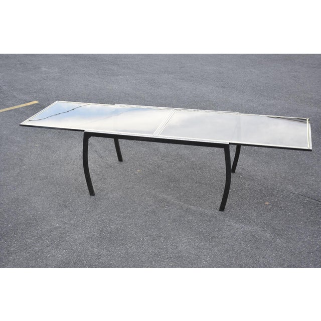 A vintage modern expanding dining table made of a gunmetal metallic chrome frame and two smoked glass inserts with brass...