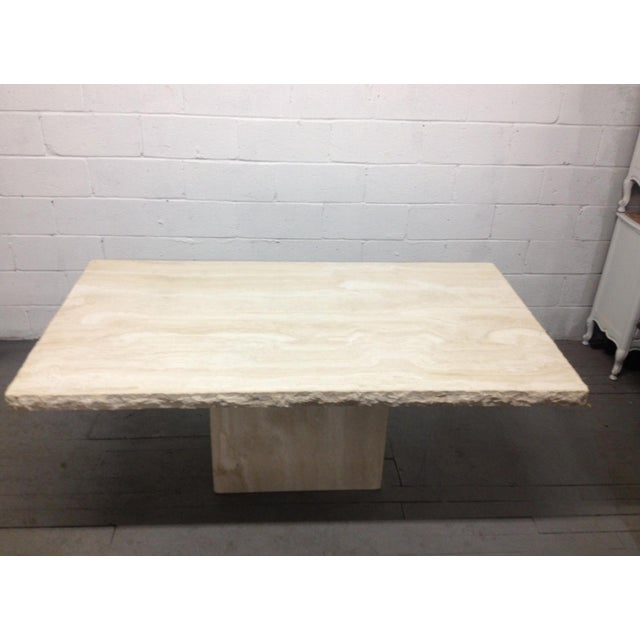 Large Italian travertine table or dining table. The top and the base has a smooth finish. The edges of the top is rough....
