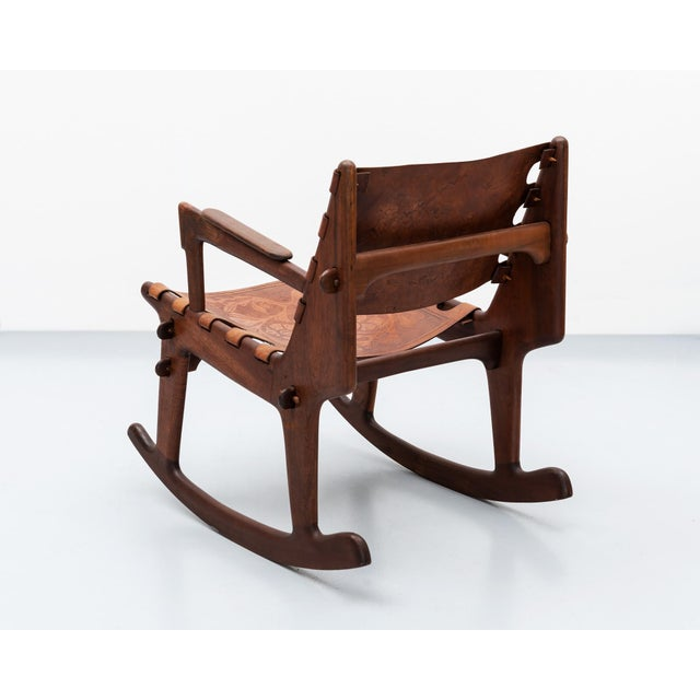 A rocking chair by South American modernist Angel Pazmino for Muebles de Estilo in solid rosewood with heavy, hand-tooled...