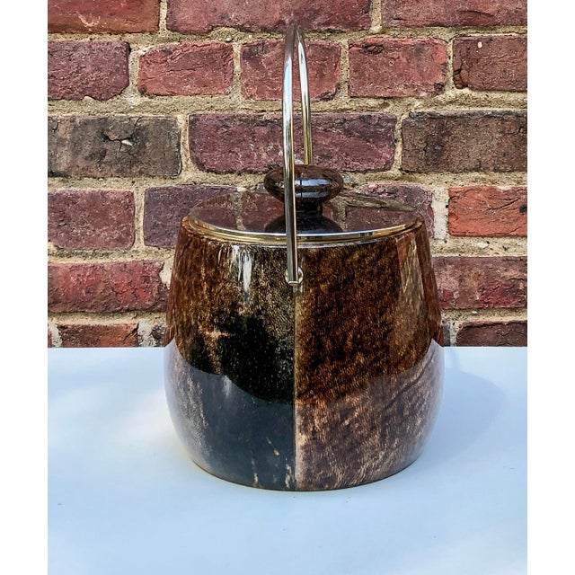 A striking and jewel like tone ice bucket by designer Aldo Tura in goatskin and polished brass. Maker's label on base of...