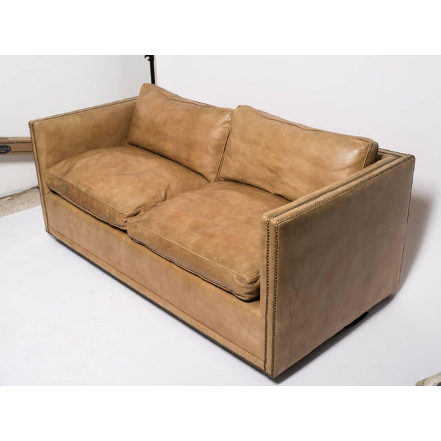 1970s down filled leather nailhead cube settee. There is a small tear below the cushion that needs to be glued down.