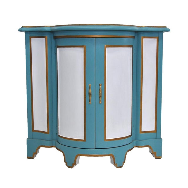 Vintage Hollywood Regency style demilune cabinet attributed to Baker. Hand painted, the two doors open to reveal a shelf.