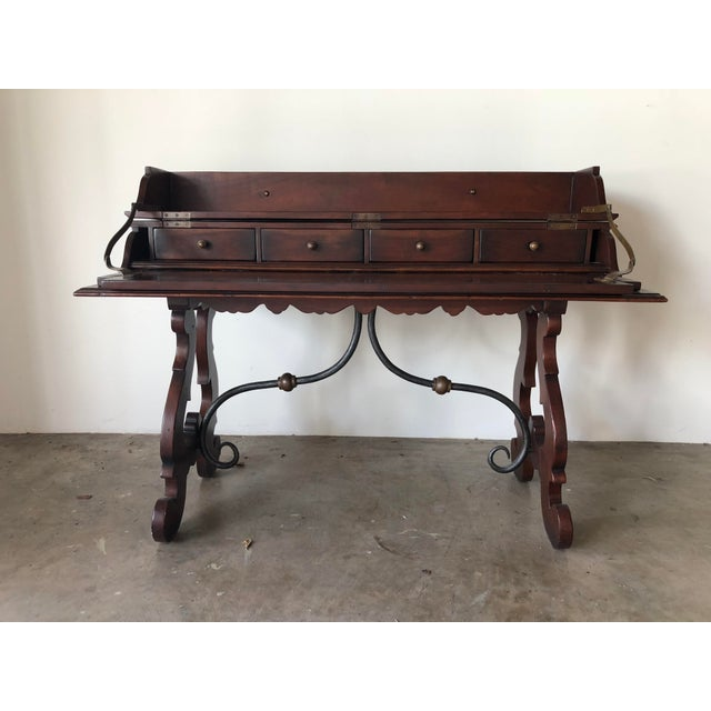 A charming style lift top desk or writing table. Wood and wrought iron detail. Scroll feet.